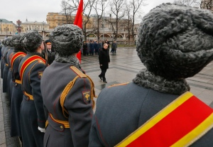 Flanked by Russian soldiers, Vladimir Putin lays a wreath near the Kremlin a year ago today